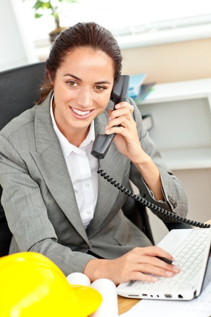 Confident female architect talking on phone and using her laptop in her office Stock Photo - 10242945