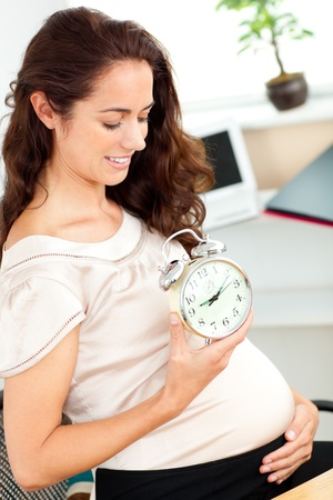 Pregnant businesswoman holding an alarm clock and looking at her belly in her office photo