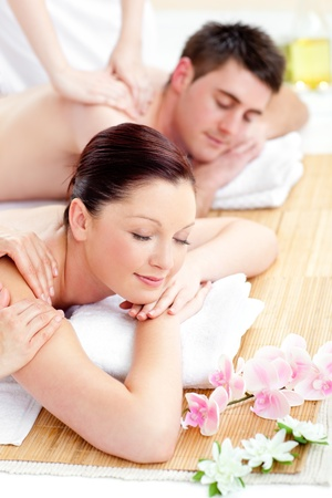 Young caucasian couple receiving a back massage photo