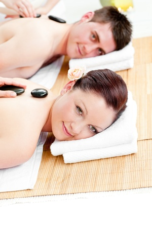 massage stones: Cute young couple receiving a back massage with hot stones