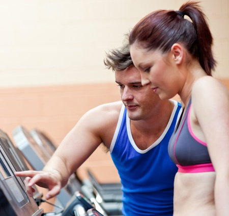 Pretty athletic woman standing on a running machine with her personal coach photo