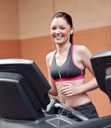 musculation: Radiant athletic woman with earphones exercising on a running machine