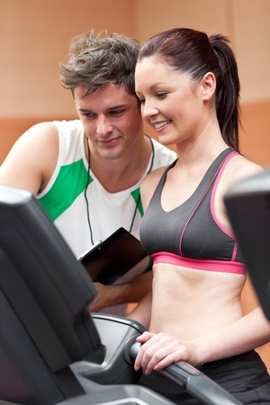 musculation: Joyful female athlete standing on a running machine with her personal coach