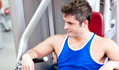 Relaxed young man using a bench press photo