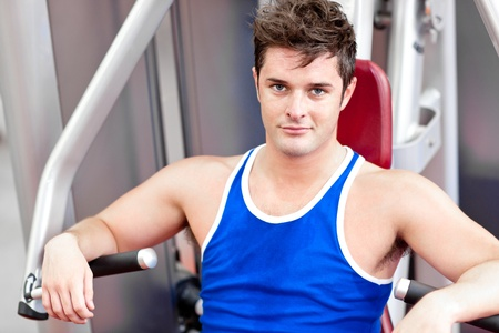 Self-assured young man using a bench press photo