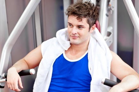 musculation: Cute relaxed man with a towel using a bench press