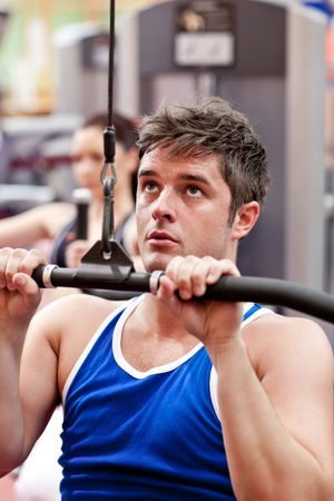 Muscular male athlete practicing body-building photo
