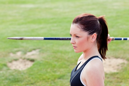 Concentrated athletic woman ready to throw the javelin photo