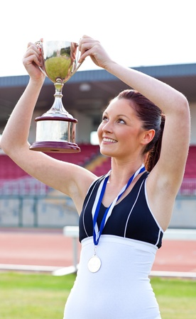 Joyful female athlete holding a trophy and a medal Stock Photo - 10243788