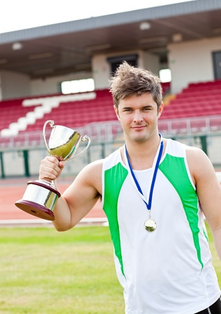musculation: Delighted male athlete holding a cup and a medal standing