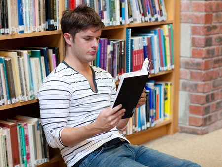 librarian: Handsome young man reading a book sitting on the floor