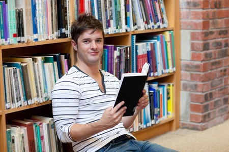 Handsome male student reading a book sitting on the floor photo