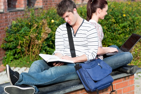 Couple of students using a laptop and reading a book sitting photo