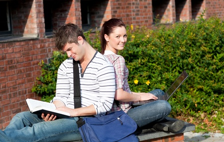 Lovely couple of students using a laptop and reading a book photo