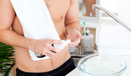 Close-up of a young muscular man ready to shave in the bathroom photo