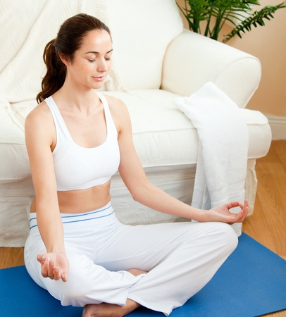 yoga pillows: Concentrated woman doing yoga sitting in her living-room Stock Photo