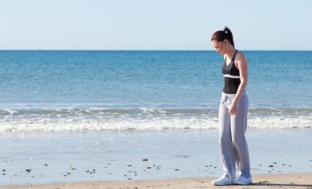 Bright woman standing on the beach and listening to music Stock Photo - 10243516