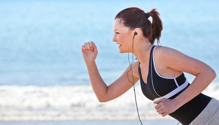 Close-up of a sporty woman running on the beach and listening to music photo