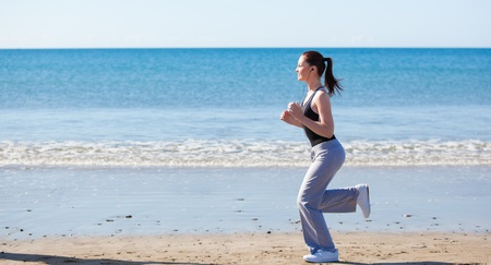 Sporty woman running on the beach and listening to music Stock Photo - 10243626