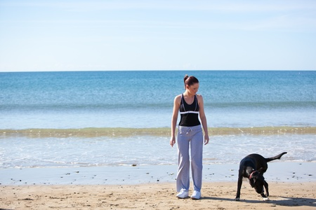 Young sporty woman with a dog on the beach Stock Photo - 10244001