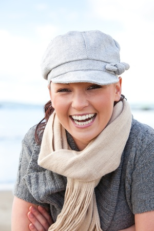 Laughing caucasian woman with cap and scarf standing on the beach Stock Photo - 10244103
