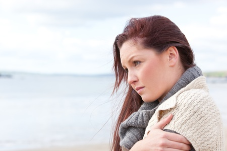 worried: Unhappy woman wearing hat and scarf on the beach
