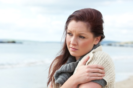 worried woman: Unhappy woman wearing sweater on the beach and getting cold Stock Photo