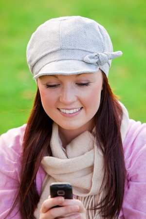 Pretty young woman wearing cap and scarf sending a message with her cellphone on the grass photo