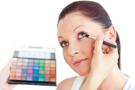 Charming woman being applied eye makeup photo