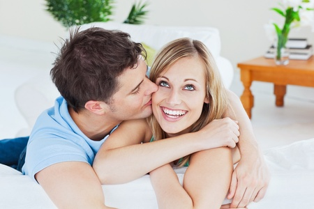 Handsome man kissing his joyful girlfriend both lying on the sofa photo