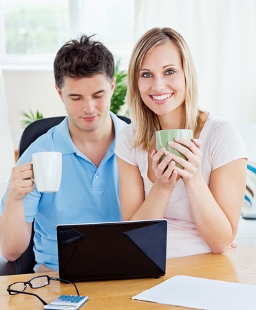 Young couple drinking coffee and working together on the laptop  photo