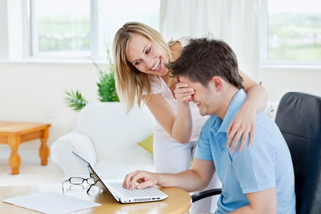 Bright caucasian couple having fun in front of a laptop Stock Photo - 10244420