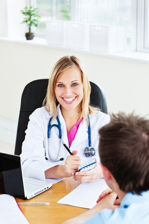 Smiling female doctor writing a prescription for her patient in the office photo
