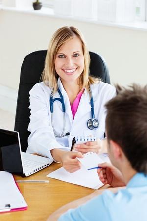 recetas medicas: Alegre mujer m�dico que den una receta a su paciente en la oficina