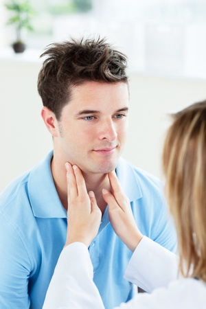 physical exam: Primo piano di una dottoressa toccando la gola di un paziente in ufficio Archivio Fotografico