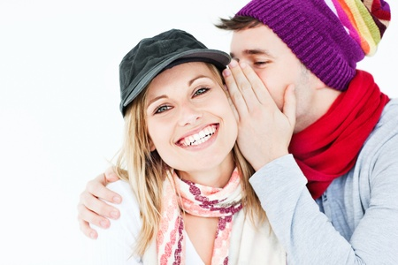 convivial: Young man with cap whispering something to his female friend