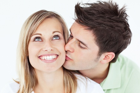 cheek to cheek: Careful man kissing his smiling girlfriend against a white background