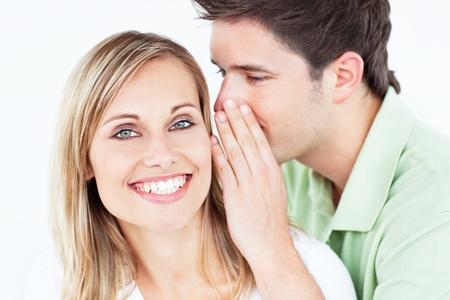 softly: Handsome man whispering something to his girlfriend against a white background Stock Photo