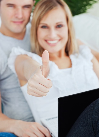 two thumbs up: Young couple working on a laptop with girlfriend doing a thumbs-up