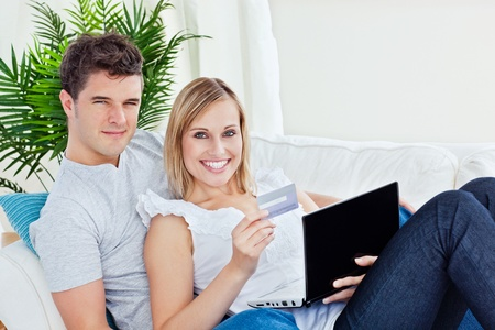 Young couple with laptop and credit card bying online lying in the living-room photo
