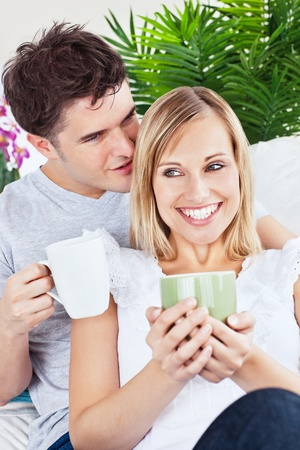 Handsome man whispering something to his girlfriend while drinking coffee photo