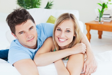 Smiling beatiful couple sitting on a sofa photo