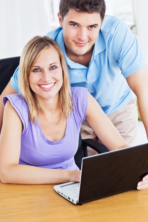 Smiling couple using computer on the desk  photo