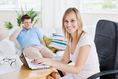 Beautiful couple. Woman using laptop  photo