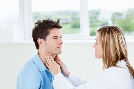 Female doctor examinating her male patient  Stock Photo - 10244180