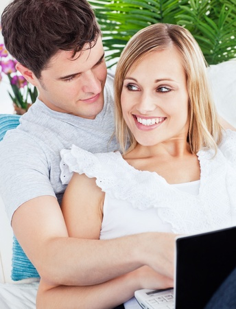 Portrait of a Happy young couple sitting on a sofa using laptop photo