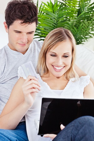 young couple using laptop siting on a sofa  photo