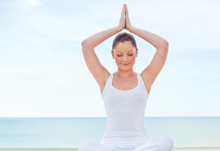 Concentrated woman practicing yoga by the beach  photo