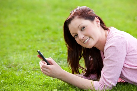 Attrative young pregnant woman lying on the grass texting photo