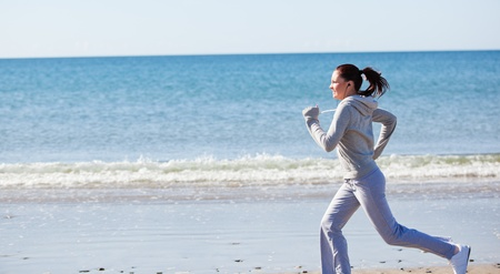 Attractive woman running on the beach  photo